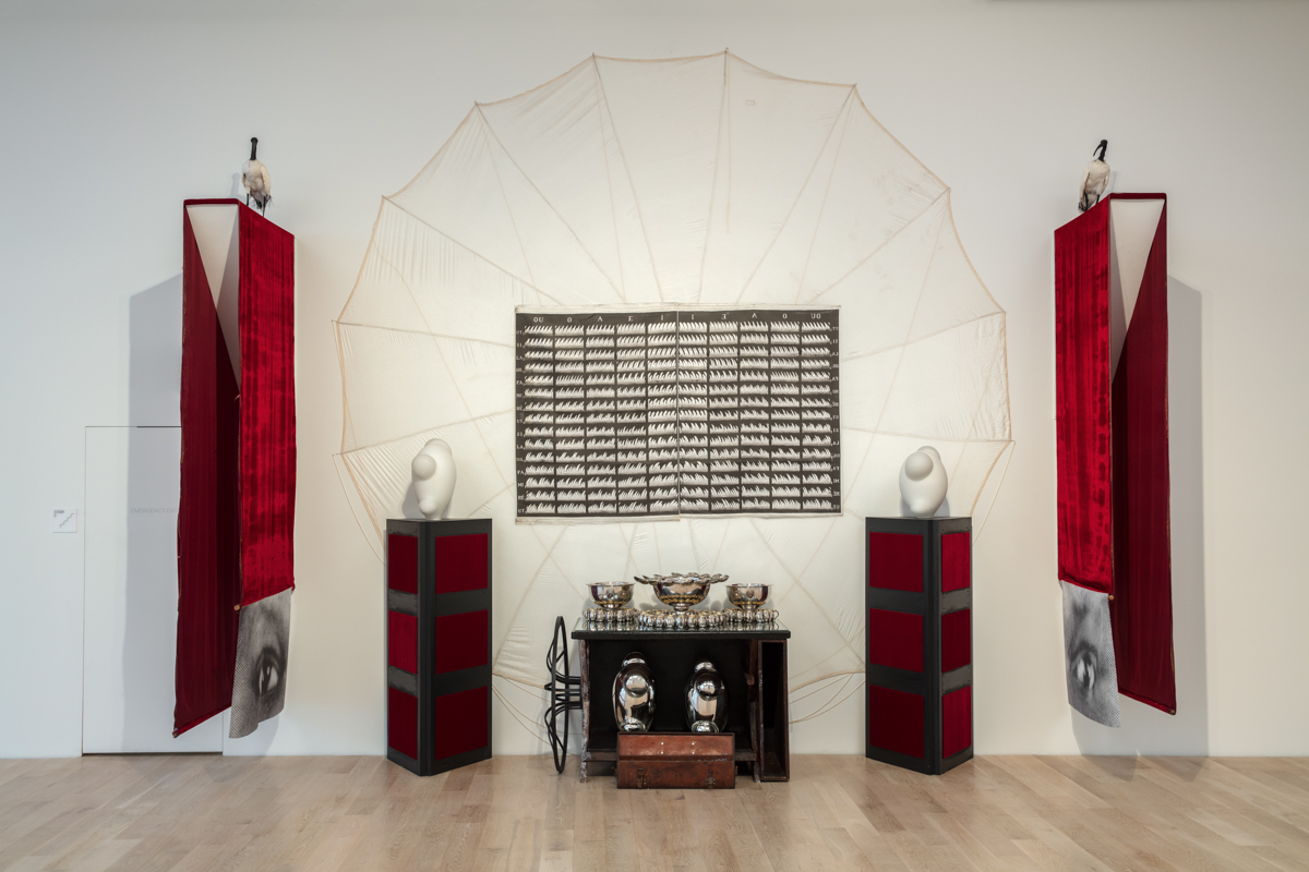 This is image of a large installation that takes up most of a gallery wall. It comprises silver bowls and utensils (some modified), glass marbles, leather case, honey, nylon single-sided flags, taxidermied birds, sewing machine, instrument stand, and inkjet print. It's size is approximately 240 x 216 x 144 in.