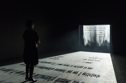 There is a viewer standing on a scrolling letter from Ghandi to Hitler. The letter has been projected on a screen of mist and the viewer in the gallery is standing on the moving image projected on the floor.