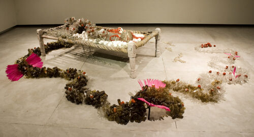 This is an installation on the gallery floor. There is a raised platform and around it, arrangements of objects. The materials in the work: Light bulbs, pigeon feathers, steel carbon wire, copper, silk thread, glass beads, cowrie shells, trim, wedding sari, seed beads, wood, horn, fleece. It measures 38 x 34 x 23 in.