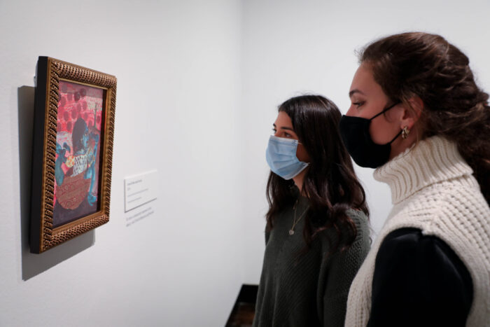 Two women with masks viewing art