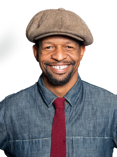 Thaxton Waters has a broad smile on his face. He's wearing a jaunty snap brim hat and wears a denim shirt and red tie.